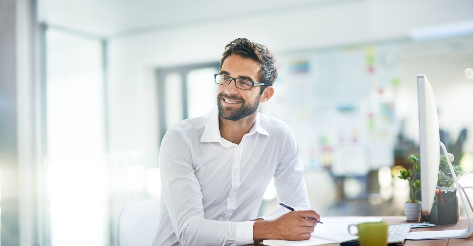 homme souriant en chemise blanche assis devant un ordinateur
