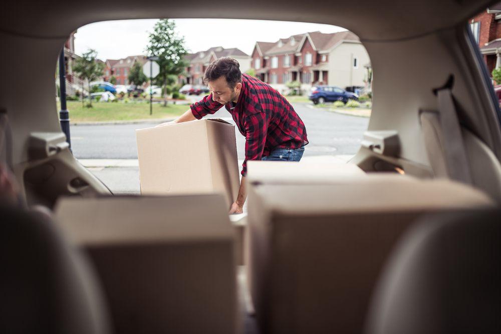Un homme sort des boîtes de déménagement de son auto