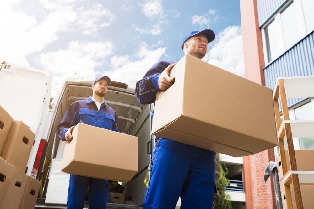 Deux hommes en uniforme bleu transportent des boîtes
