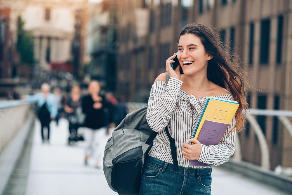 Jeune femme marchant avec ses livres scolaires