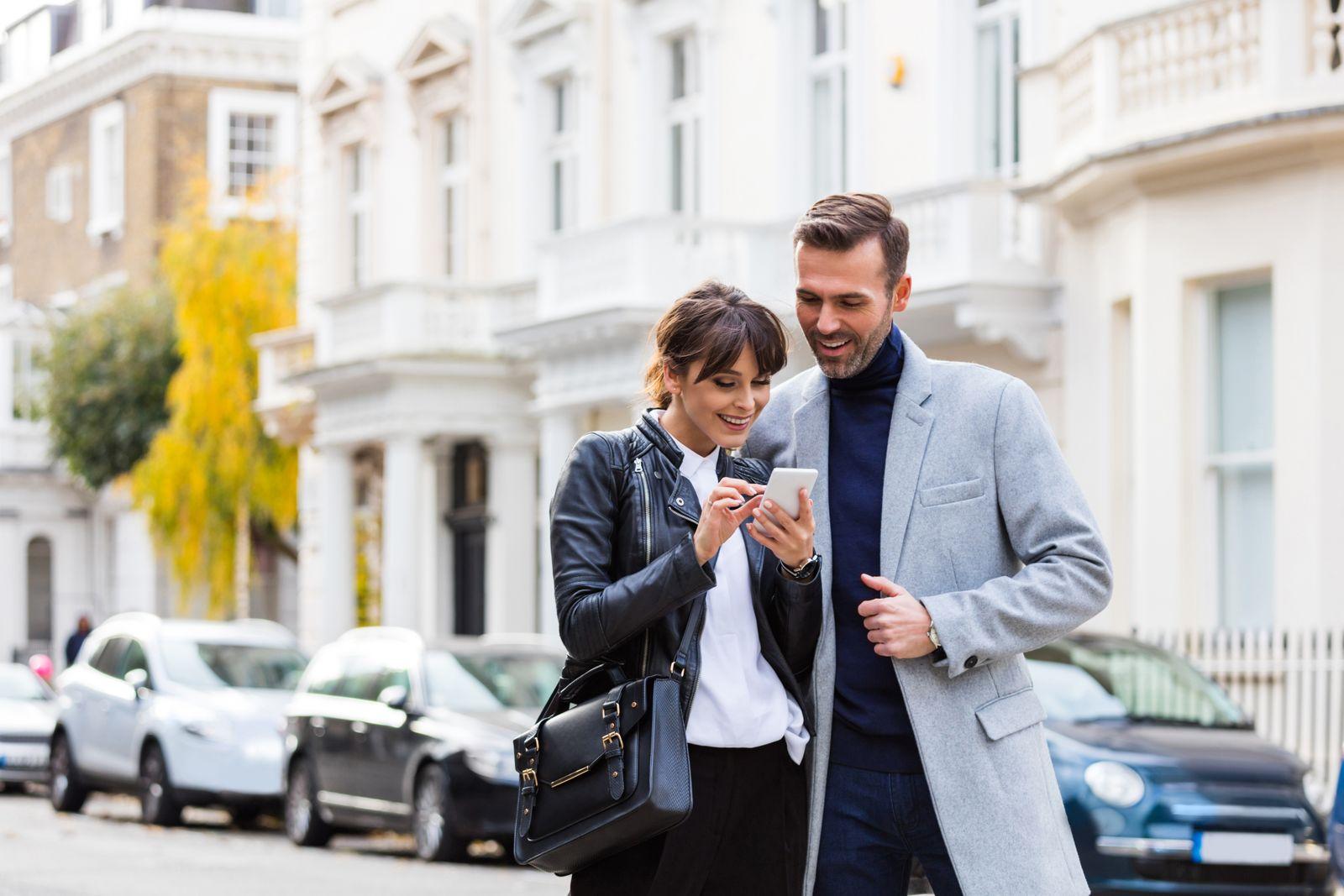 couple heureux recherche sur un cellulaire dans un quartier résidentiel