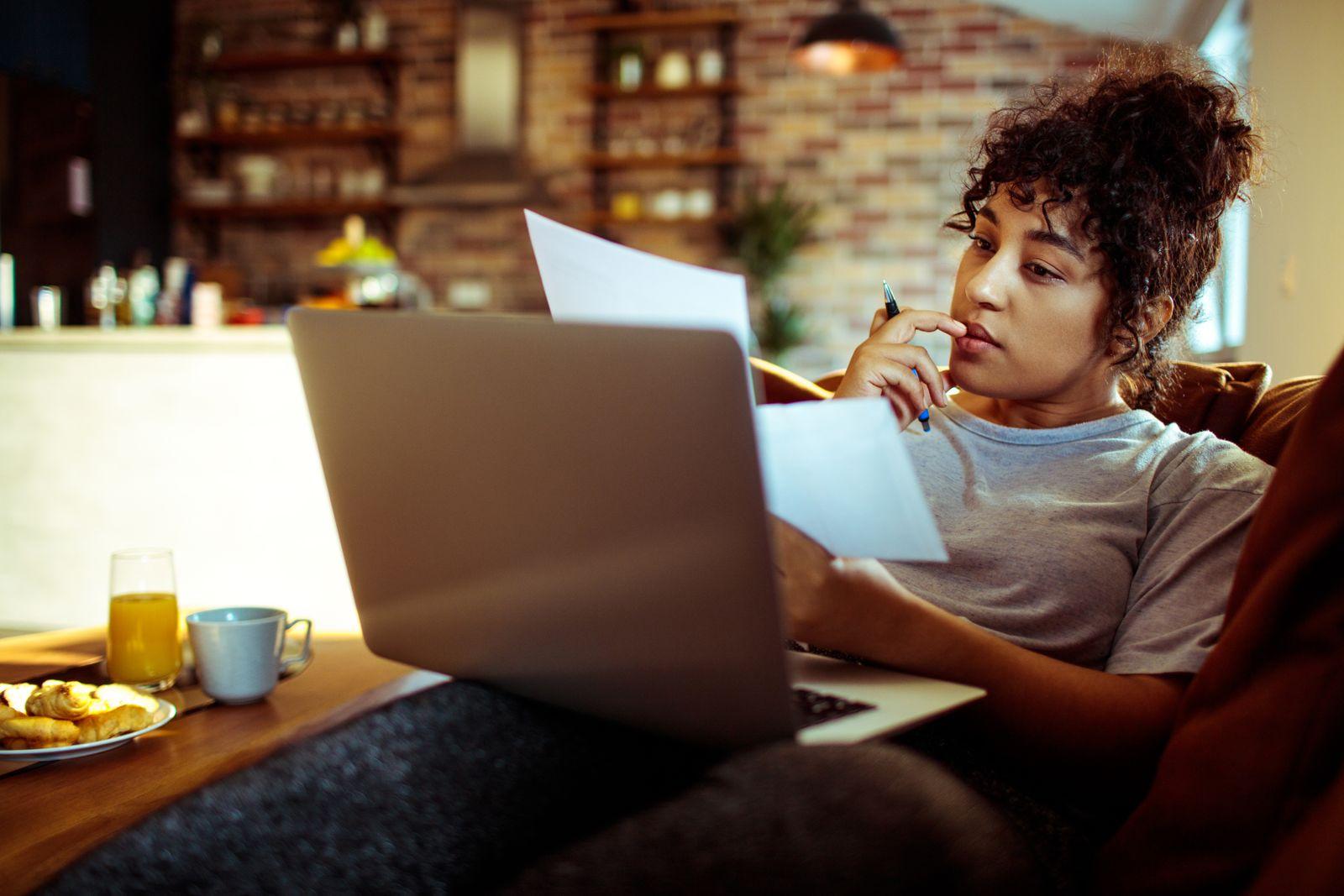 femme recherche à l'ordinateur sur son divan