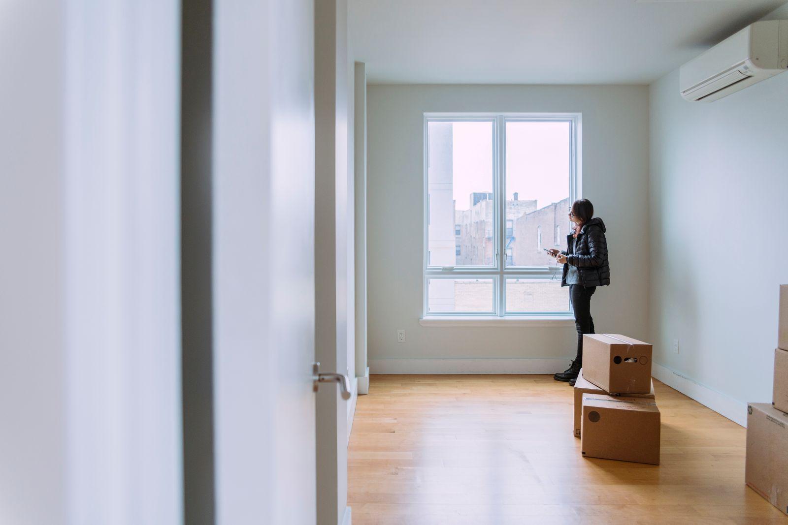 jeune femme quitte son appartement vide avec boîtes