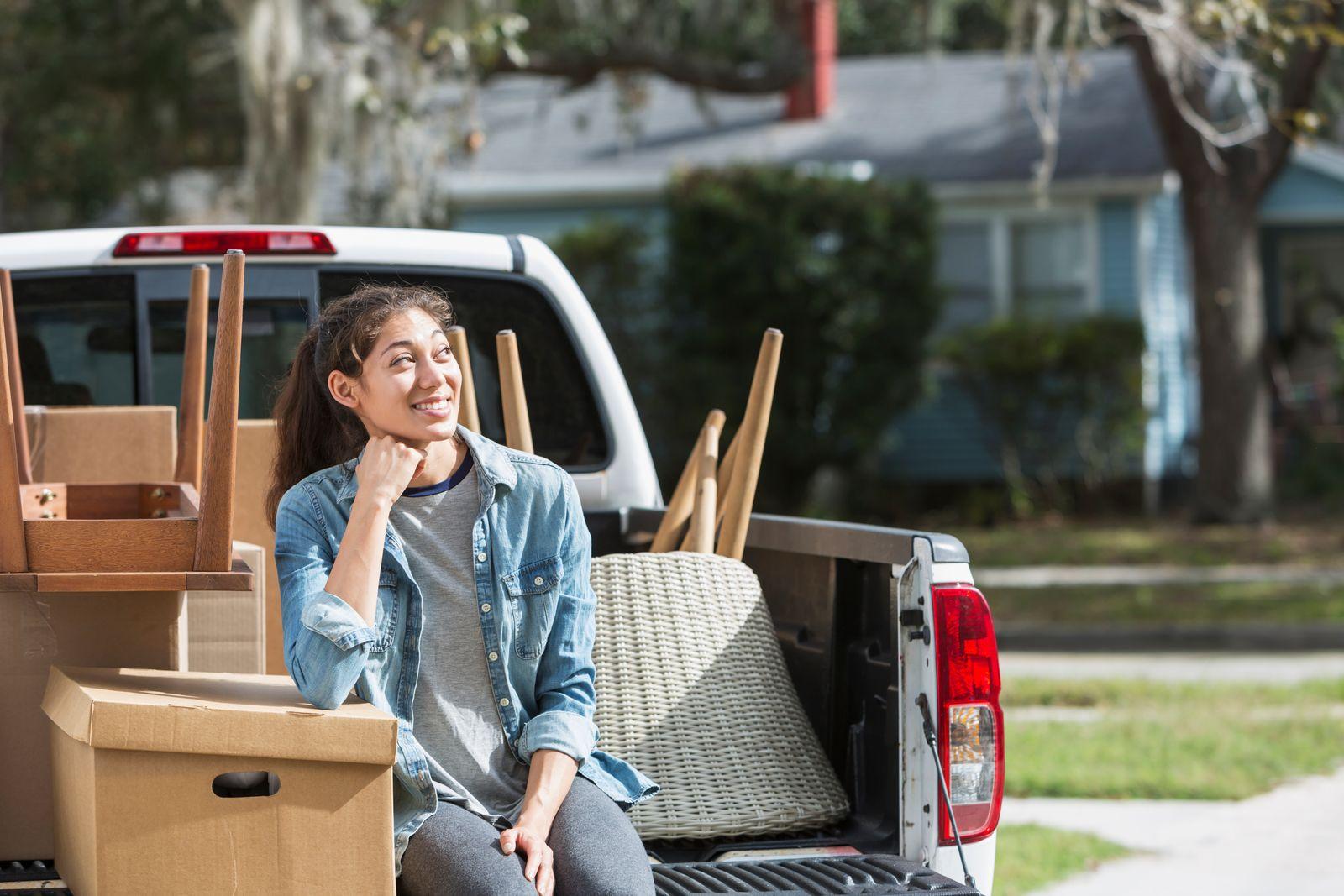 jeune femme assise dans une camionnette avec des boîtes de déménagement