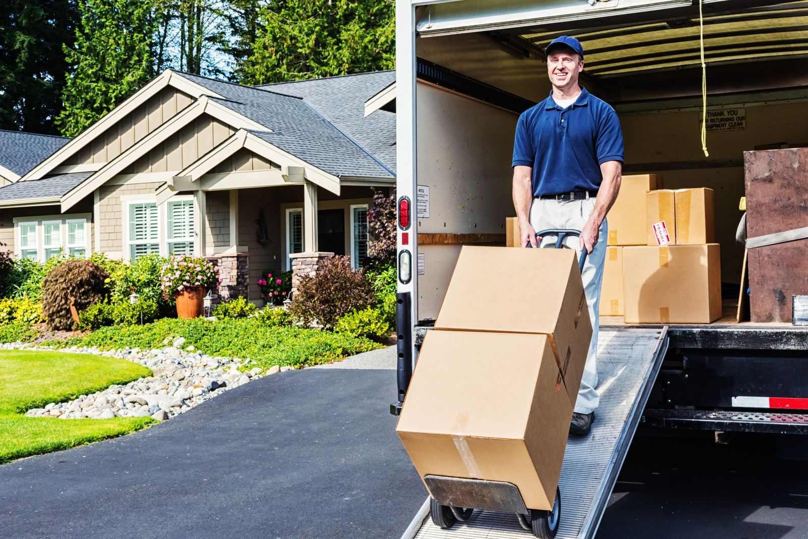 homme compagnie de déménagement embarquant des boîtes dans un camion de déménagement