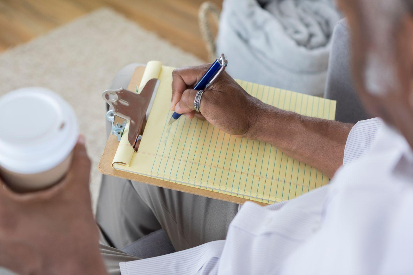 homme écrivant une liste sur un bloc-notes avec un café dans la main