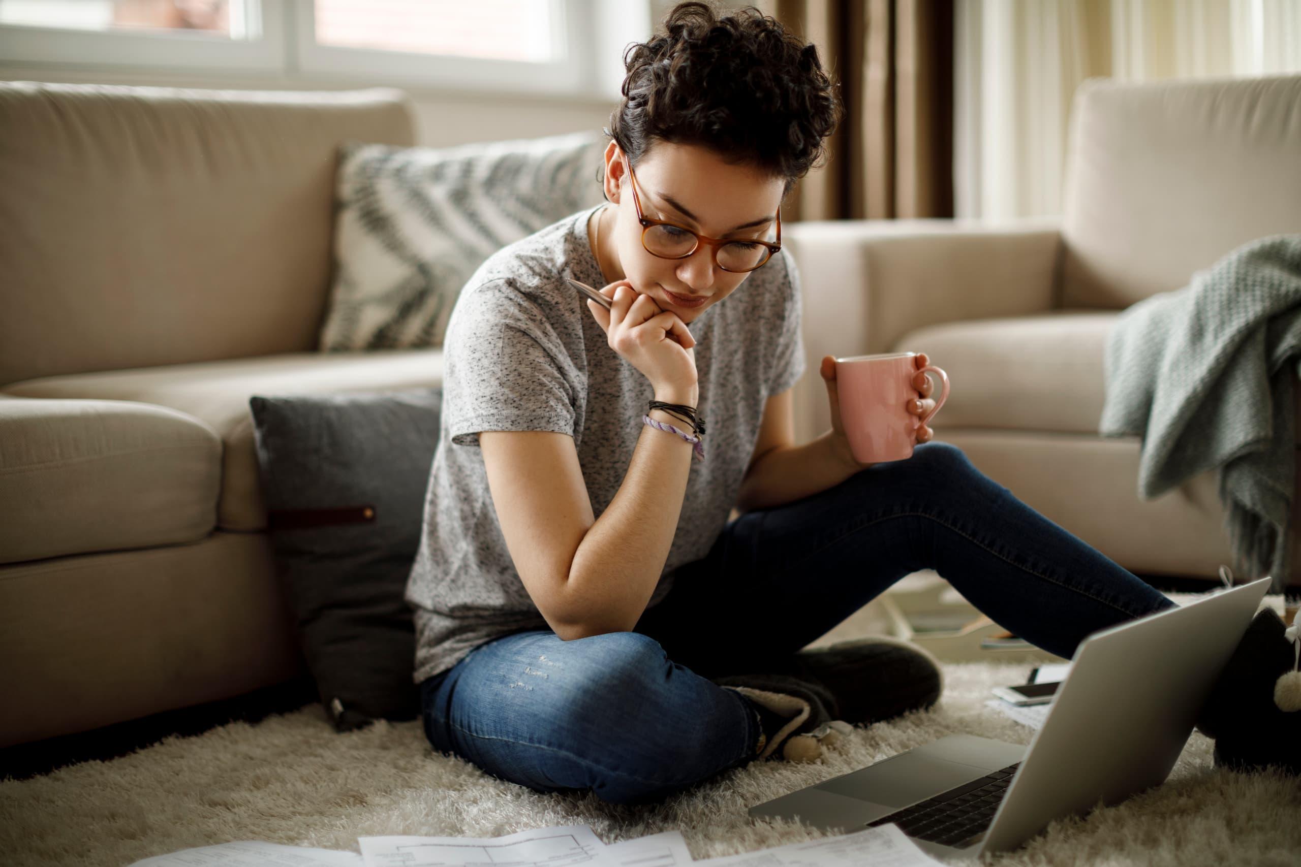 Femme pensive sur le sol avec un ordinateur portable